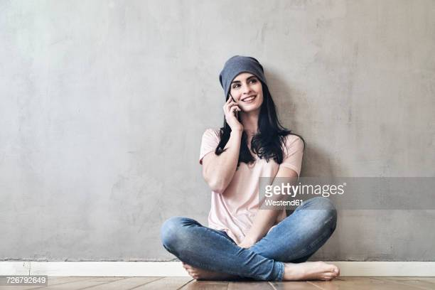 Smiling young woman sitting on the floor talking on cell phone