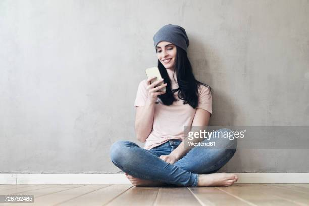 Smiling young woman sitting on the floor using cell phone