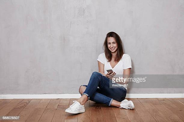Smiling young woman sitting on the floor with cell phone