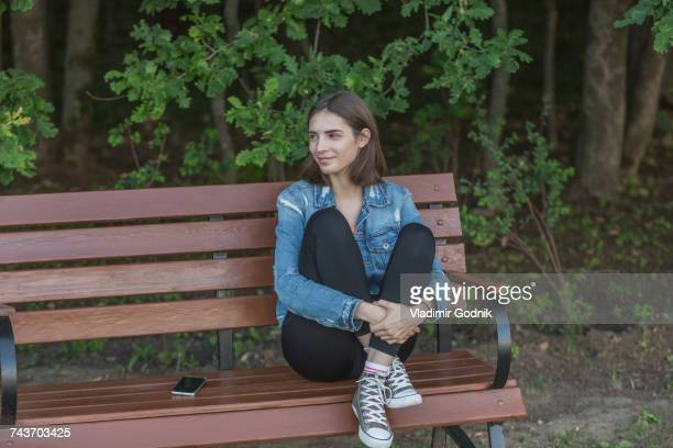 Smiling young woman sitting on wooden bench against trees at park