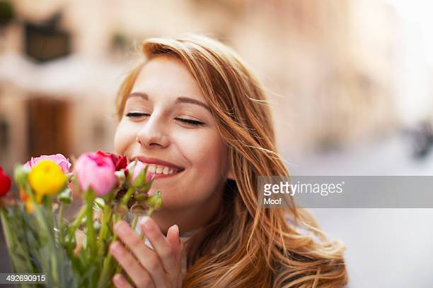 Smiling young woman smelling a bunch of flowers