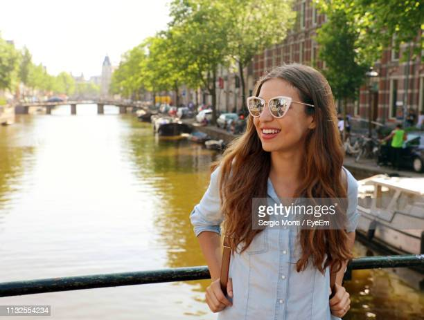smiling young woman standing against canal - amsterdam stock pictures, royalty-free photos & images