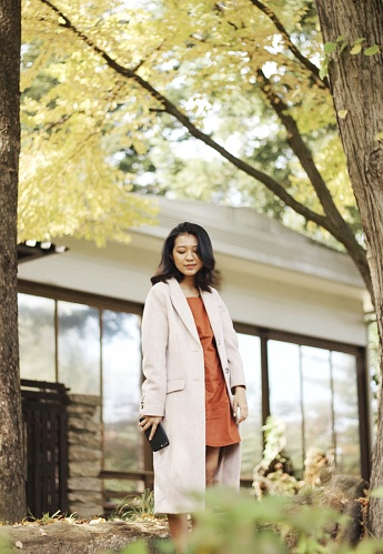 Smiling Young Woman Standing Against House - gettyimageskorea