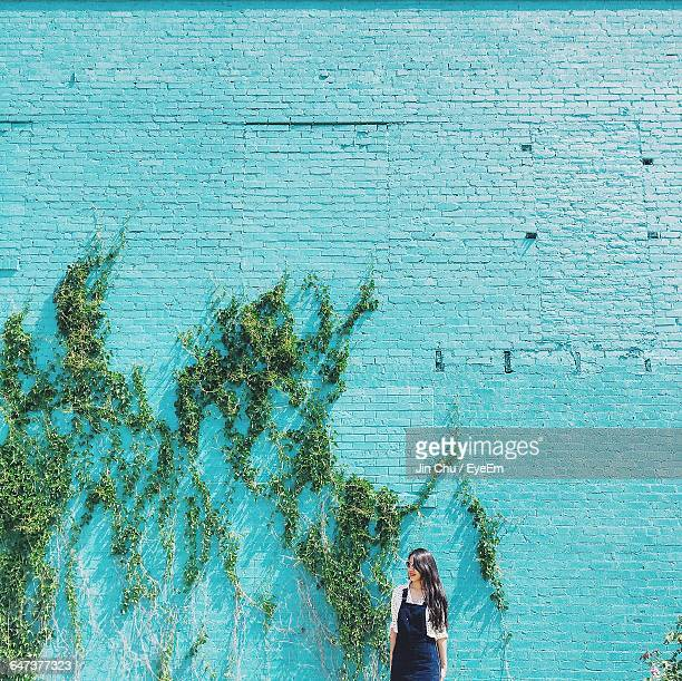 Smiling Young Woman Standing Against Turquoise Wall