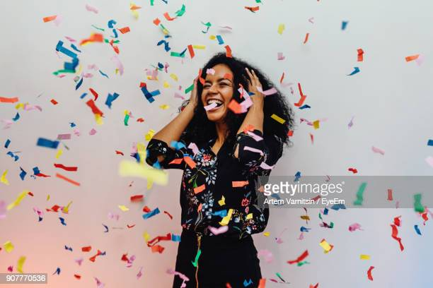 smiling young woman standing amidst confetti against wall - 祝う ストックフォトと画像