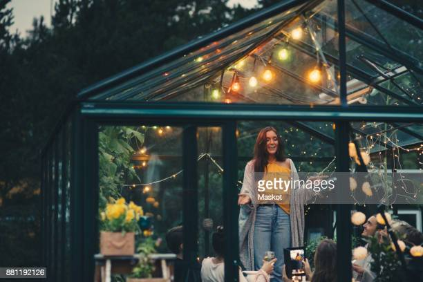 smiling young woman standing amidst friends in glass conservatory at back yard - middelgrote groep mensen stockfoto's en -beelden