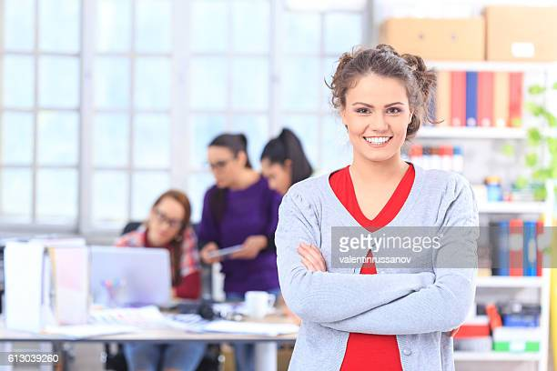 Smiling young woman standing arms crossed in the office
