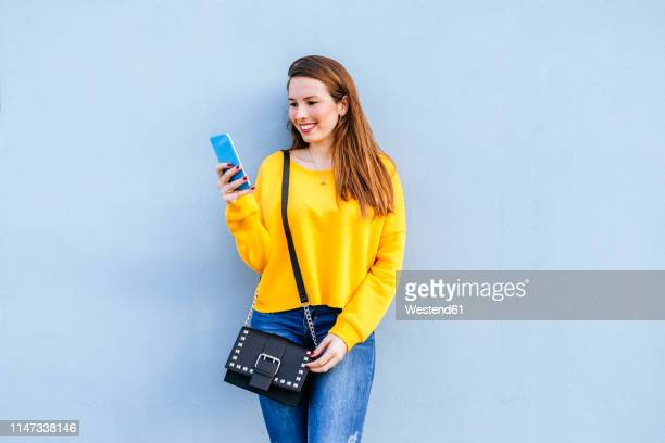 smiling young woman standing at a wall using cell phone - blue purse stock pictures, royalty-free photos & images