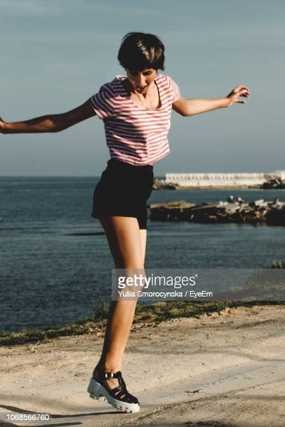 smiling young woman standing at beach - sandal stock pictures, royalty-free photos & images