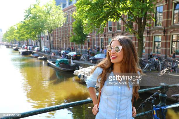 Smiling Young Woman Standing By Railing On Footbridge Over Canal