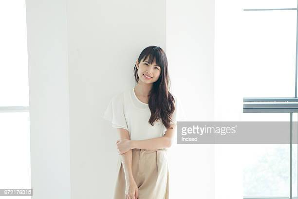 Smiling young woman standing by wall