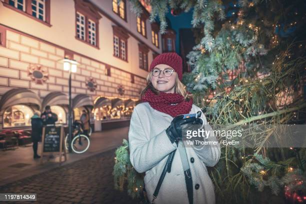 smiling young woman standing in city at night - val thoermer stock-fotos und bilder