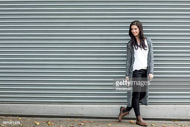 Smiling young woman standing in front of roller shutter