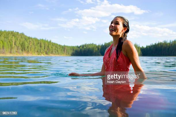 Smiling young woman standing in lake