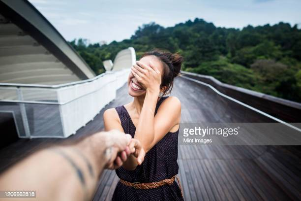 smiling young woman standing on a bridge, covering her face, holding man's hand. - love stock pictures, royalty-free photos & images