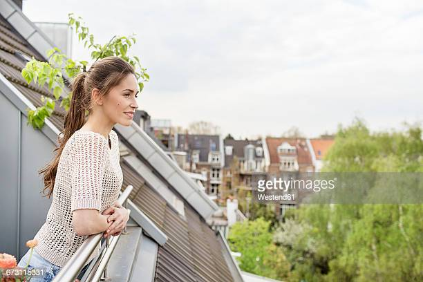 Smiling young woman standing on balcony
