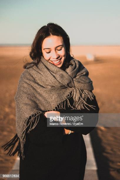 smiling young woman standing on beach - shawl stock pictures, royalty-free photos & images