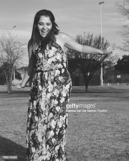 F Smiling Young Woman Standing On Field At Park