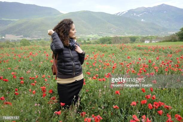 Smiling Young Woman Standing On Field With Flowering Plants Against Sky