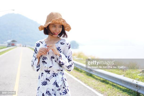 smiling young woman standing on road against sea - cha cha stock photos and pictures