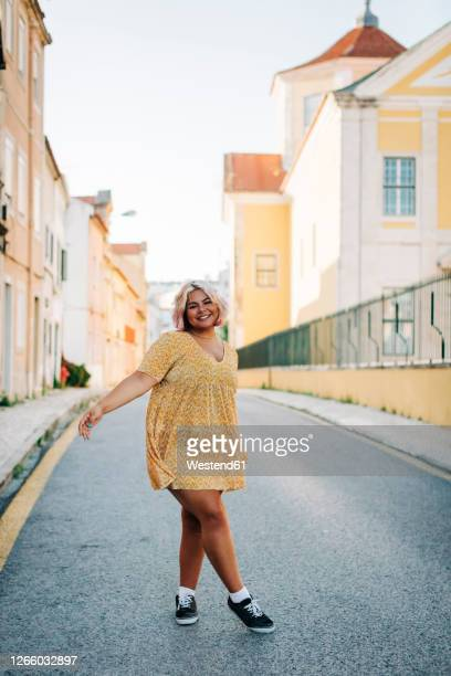 smiling young woman standing on road in city - plus size model stock pictures, royalty-free photos & images