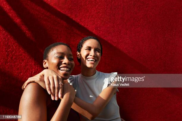 smiling young woman standing with female friend - affectionate stock pictures, royalty-free photos & images