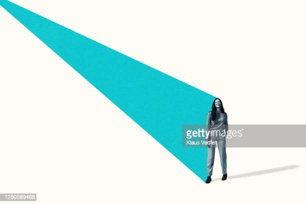 smiling young woman standing with turquoise beam - plain background stock pictures, royalty-free photos & images