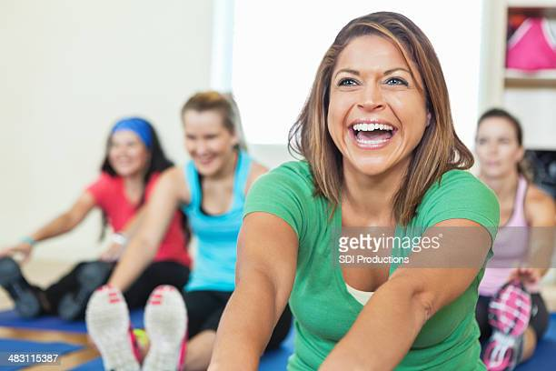 Smiling young woman stretching in fitness class