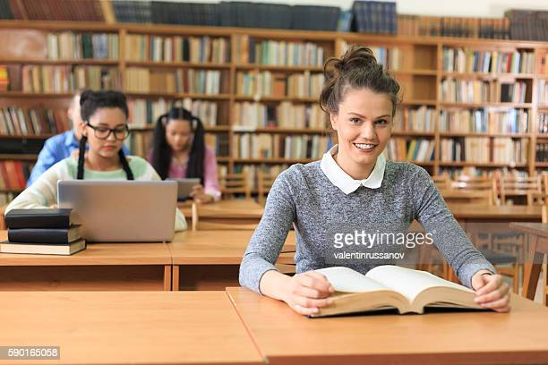 Smiling young woman studying at the library