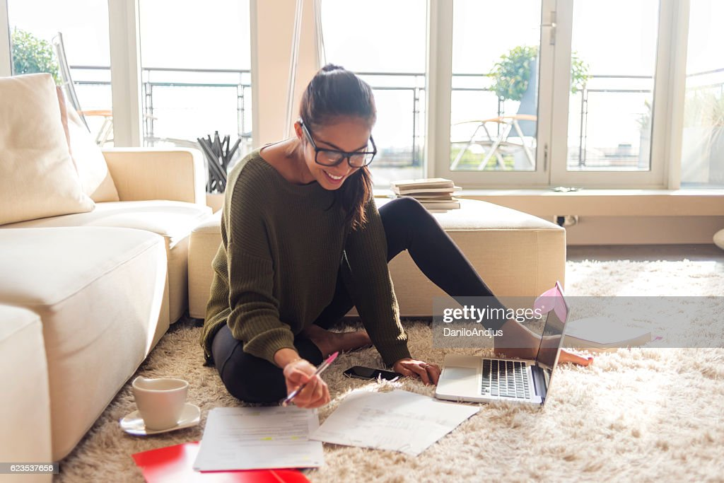 smiling young woman studying in her living room : Foto de stock