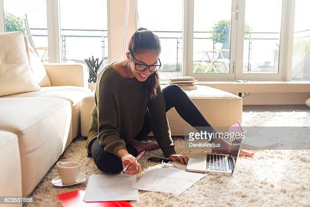 smiling young woman studying in her living room - money fotografías e imágenes de stock