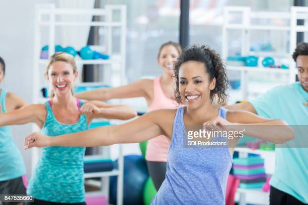 smiling young woman swings her arms during dance class at the gym - aerobics stock photos and pictures
