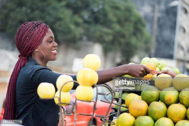 smiling young woman takes her money in the hand of the fruit seller. - femme ivoirienne photos et images de collection