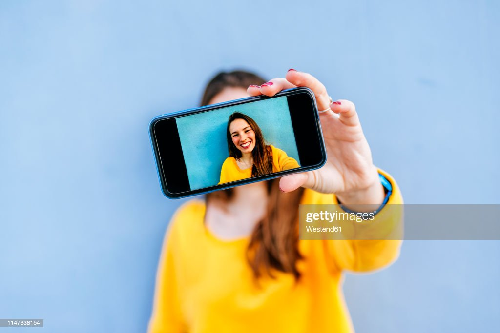 Smiling young woman taking a selfie at a blue wall : Foto de stock
