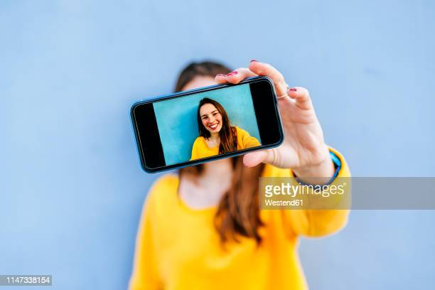 smiling young woman taking a selfie at a blue wall - mujeres fotos fotografías e imágenes de stock