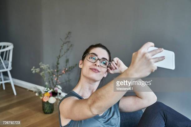smiling young woman taking a selfie at home - eitelkeit stock-fotos und bilder