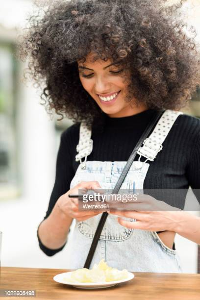 Smiling young woman taking photo of potato chips with cell phone
