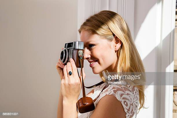 Smiling young woman taking picture with old camera