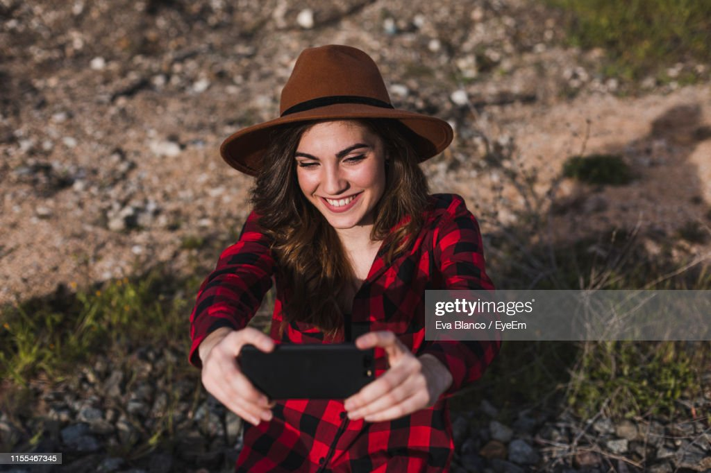 Young Woman With Face Mask Taking Selfie In Park High-Res