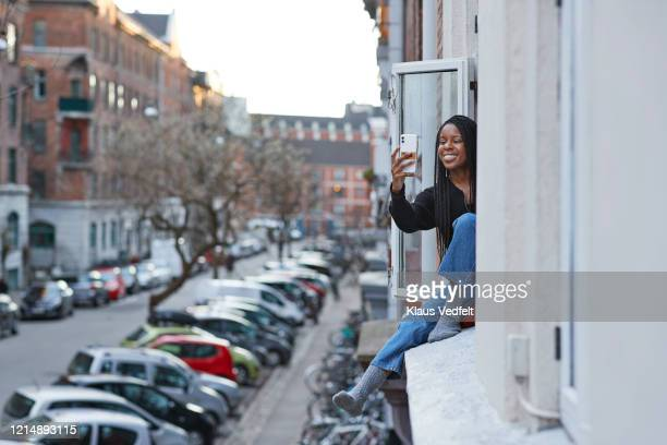 smiling young woman taking selfie in apartment window - photo messaging stock pictures, royalty-free photos & images