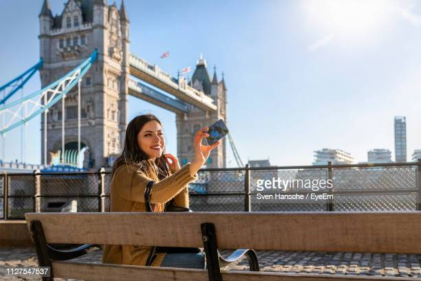 smiling young woman taking selfie while sitting on bridge in city against sky - famous place stock pictures, royalty-free photos & images
