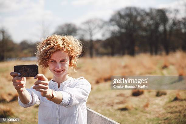 smiling young woman taking selfie while standing at field - bortes fotografías e imágenes de stock