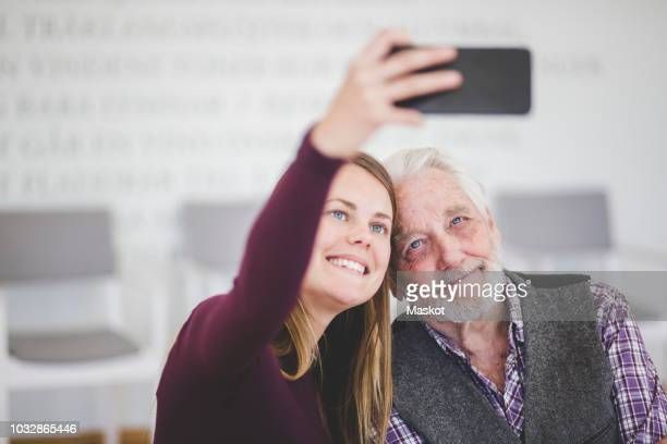 smiling young woman taking selfie with grandfather while sitting in nursing home - pareja hombre mayor y mujer joven fotografías e imágenes de stock
