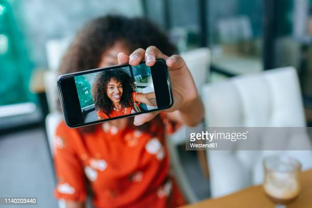 smiling young woman taking selfie with smartphone, close-up - mostrare foto e immagini stock