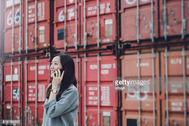 Smiling young woman talking on cell phone in container terminal