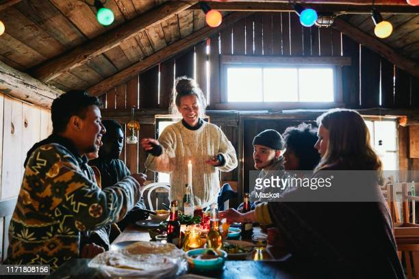 smiling young woman talking while enjoying meal with friends in cottage - log cabin stock pictures, royalty-free photos & images