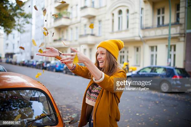 Smiling Young Woman Throwing Leaves On Car At Street