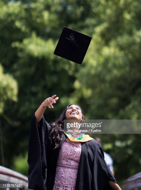 smiling young woman throwing mortarboard - graduation stock pictures, royalty-free photos & images