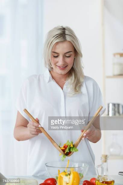 Smiling young woman tossing fresh salad on kitchen counter at home