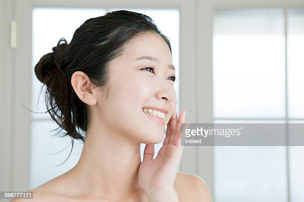 Smiling young woman touching face